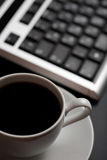 Cup of coffee and keyboard (shallow DOF) Royalty Free Stock Photos