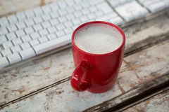 Cup of coffee beside keyboard on wooden table Royalty Free Stock Photo