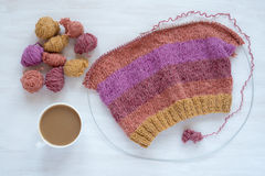 Cup of coffee and knitting on white background Stock Images