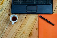 a cup of coffee with labtop and a pen with book on wood desk royalty free stock image