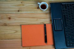 a cup of coffee with labtop and a pen with book on wood desk royalty free stock images