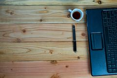 a cup of coffee with labtop and a pen on wood desk royalty free stock images