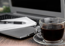 A cup of coffee. With laptop on background Royalty Free Stock Images