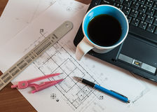 Cup of coffee on laptop with construction plans Stock Image