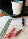Cup of coffee on laptop with construction plans Royalty Free Stock Images