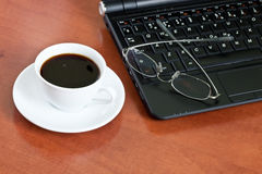 Cup of coffee with a laptop and glasses Stock Photo