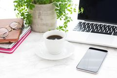 Cup of coffee, laptop, glasses and alarm clock. White cup of black coffee on saucer, open laptop, glasses and beautiful classic alarm clock with white face next royalty free stock image