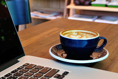 A cup of coffee with laptop. Coffee Latte art with laptop Stock Images