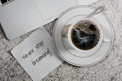 Cup of coffee, laptop and a napkin with motivation slogan. Cup with espresso coffee, laptop and a napkin with motivation slogan on table in cafe - top view royalty free stock photos