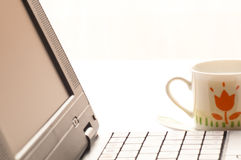 Cup of coffee and laptop on the table. Detail of a laptop with a cup of coffee next to it Royalty Free Stock Photography