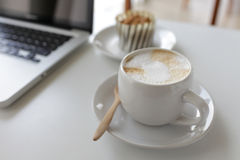 A cup of coffee and a laptop. On a white desk Stock Images