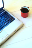Cup of coffee and laptop. On white wooden table Stock Images