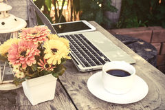 A cup of coffee and laptop on wood floor with flower Stock Photo
