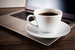 Cup of coffee and laptop Stock Image