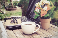 Cup of coffee and laptop on wooden table Stock Photos