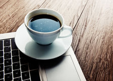 Cup of coffee and laptop on wooden table. Stock Images