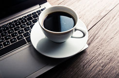 Cup of coffee and laptop on wooden table. Stock Photography