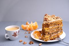A cup of coffee and large piece of homemade cake on a porcelain saucer with nuts and mandarin stock photo