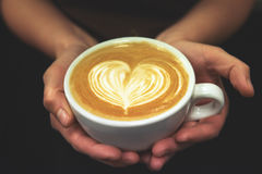 Cup of coffee. Latte art made by barista focus in milk and coffe Stock Photo