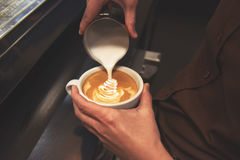 Cup of coffee. Latte art made by barista focus in milk and coffe Royalty Free Stock Image
