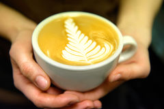 Cup of coffee. Latte art made by barista focus in milk and coffe Stock Photos