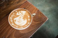 A cup of coffee latte art swan in the corner of a wooden table stock photography