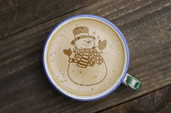 Cup of coffee latte art on wood table. Foam form of snowman. Royalty Free Stock Photo