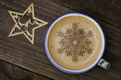 Cup of coffee latte art on wood table. Foam form of star and woo Stock Images