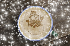 Cup of coffee latte art on wood table and snowy background. Foam. Form of snowman stock photo