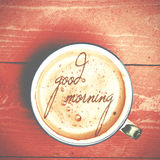 Cup of coffee latte, cappuccino on a pink wood table. Words good. Morning written on a coffee royalty free stock image