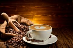 Cup of coffee latte and coffee beans on old wooden Stock Photos