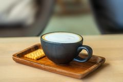 A Cup of coffee latte with cracker. close up. light breakfast. stock photography