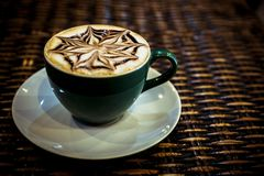 Cup of coffee latte with design art in froth, on a. Wooden table. Close up Stock Images