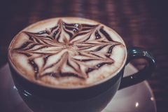 Cup of coffee latte with design art in froth, on a. Wooden table. Close up Royalty Free Stock Image