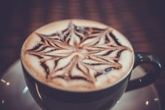 Cup of coffee latte with design art in froth, on a. Wooden table. Close up Royalty Free Stock Photos