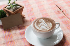 Cup of coffee latte on desk and card. On wooden desk Royalty Free Stock Image