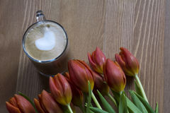 Cup of coffee latte with red fresh tulips Royalty Free Stock Photos