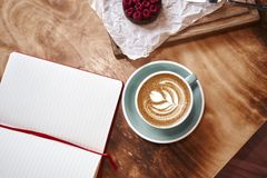 Cup of coffee latte on wooden table or background from above. Having lunch in cafe. Opened notebook, space for design template Royalty Free Stock Photography