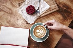 Cup of coffee latte on wooden table or background from above. Having lunch in cafe. Opened notebook, space for design template Royalty Free Stock Images