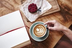 Cup of coffee latte on wooden table or background in woman hands from above. Having lunch in cafe. Opened notebook, space for desi Stock Images