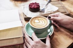 Cup of coffee latte on wooden table or background in woman hands from above. Having lunch in cafe. Royalty Free Stock Photo