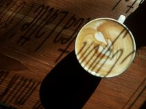 A cup of coffee latte, on the wooden table. A cup of cafe latte on the wooden table in the morning light, with a shadow of text on the window Stock Photo