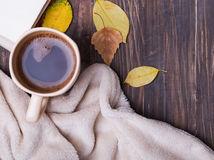 Cup of coffee, leaves and blanket on the wooden background Royalty Free Stock Photography