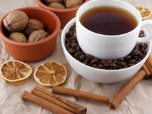 Cup of coffee with lemon, beans and cinnamon on old paper Royalty Free Stock Photos