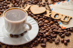 Cup of coffee and a letter on the table Stock Image