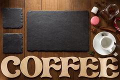 Cup of coffee and letters on wood Royalty Free Stock Image
