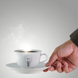 A cup of coffee with light bulb. Hand and a cup of coffee with light bulb drawing as concept Royalty Free Stock Photos