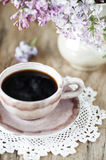 Cup of coffee and lilac flowers bouquet Royalty Free Stock Photography