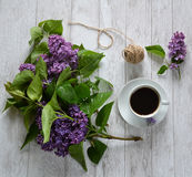 A cup of coffee and lilacs on the table. Stock Photos