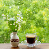 A cup of coffee and lilies of the valley on the window. Rain drops on the window. Stock Photography
